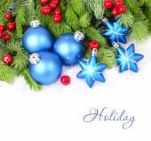 Modrý vánoční koule a hvězdy a červené bobule na nadýchané větve vánočního stromku na bílém pozadí. Vánoční pozadí s místem pro text