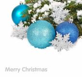 Blue Christmas balls and silvery snowflakes on snow-covered branches of a Christmas tree. A Christmas background with a place for the text.