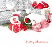 Weihnachten-Komposition mit roten Textil-Herzen, rote Geschenkbox und Christbaumschmuck im skandinavischen Stil auf einem weißen Hintergrund. Weihnachten Hintergrund mit einem Platz für den text