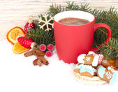 Forró csokoládé, fahéj és gyömbér cookie-k a hó fehér alapon piros bögre. A karácsonyi háttér a hely, a szöveg