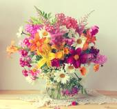 Bouquet from cultivated flowers in a jug.