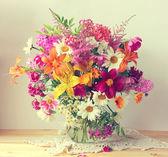 Bouquet di fiori coltivati in una brocca. Un bouquet di gigli. Una natura morta con un mazzo di fiori