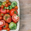 Постер, плакат: Fresh red and green tomatoes in a basket on a table