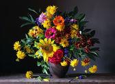 Bouquet di fiori coltivati con un girasole, Rose e altri fiori gialli e rosa contro uno sfondo scuro e la libellula seduto su un tavolo