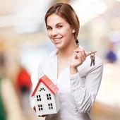 Blonde Frau mit einem kleinen Haus und Tasten