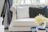 Luxusní pohovka v obývacím pokoji s žlutá květina ve váze