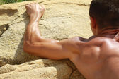 Man climbing on mountain rocks. Close up on muscular back and hands. Extreme sports outdoors. Active summer vacation