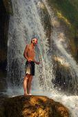 Mladý muž se radost stojící na skále vedle krásný vodopád