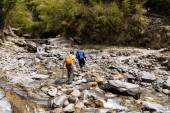 Two hikers crossing a scenic shallow rocky river