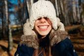 Excited happy fall woman smiling joyful and blissful pull knitted hat outside in colorful fall forest. Beautiful energetic ?aucasian young woman.