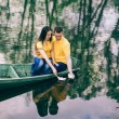 Постер, плакат: Young girl and man sitting together in old wooden boat on river