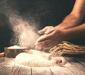 Muž připravuje těsto na dřevěný stůl v pekárně