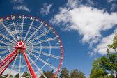 Atraktsion Ferris wheel against the blue sky