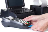 The seller takes payment by a cash register and credit card read