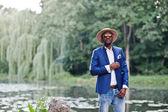 Kék kabát, kalap és sungl stílusos gazdag fekete férfi portréja