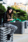 Beautiful young dark-haired woman is texting on her smartphone while sitting the bench in city park