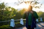 Běžné mladý muž v městě poslouchá hudbu s in-ear sluchátka při západu slunce. Měkké teplé světlo