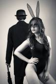 Black and white image of sexy beautiful young lady wearing bunny ears posing over male silhouette on light copy space background