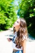 Portrait of brunette girl looking up on road between trees