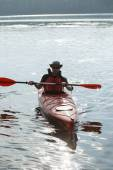 Man boating in red canoe in river at summer day