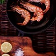 Постер, плакат: There are shrimps in a cast iron skillet