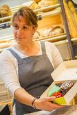 Usmívající se žena s zástěru prodávat pečivo v pekárně