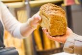 Detailní záběr ruky dávat chleba k zákazníkovi