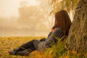 Lonely woman having rest under the tree near the water in a foggy autumn day. Lonely woman enjoying nature landscape in autumn. Autumn day. Girl sitting on grass horizontal image.