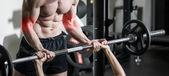 Osobní trenér s činka protahuje svaly v posilovně