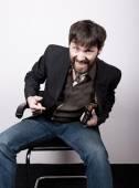 Veselý vousatý muž v bunda a džíny, sedí na židli a drží zbraň. gangster koncept. Jednání se na skript, nebezpečné známosti