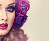 Žena s kudrnatými vlasy a květiny