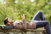 Junger Geschäftsmann entspannend mit Smartphone im Freien in der Natur