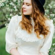Постер, плакат: Young girl in a white dress and black hat in the in the white fl