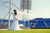 Nevěsta ve svatebních šatech na fotbalový stadion