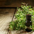 Essential oil of thyme in a bottle and fresh herb thyme