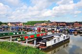 Narrowboats on their moorings in the canal basin with shops, bars and restaurants to the rear, Barton Marina, Barton-under-Needwood.