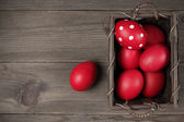 Red Easter eggs in basket — Stock Photo