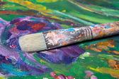 Paint brush on colorful canvas background — Stock Photo