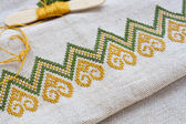 Ukrainian embroidery on the linen fabric and thread embroidery on a wooden table, selective focus — Stock Photo