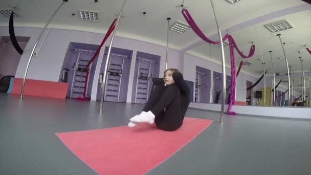 Kis lány dolgozik, nyújtó gyakorlatok az edzőteremben