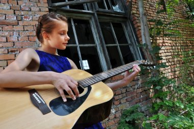 teenage girl playing acoustic guitar in the street