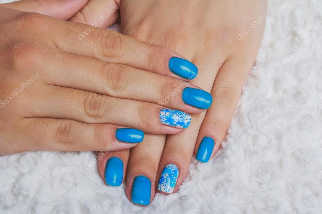 Light Blue Nail Art With Flowers On White Textile Stock Photo