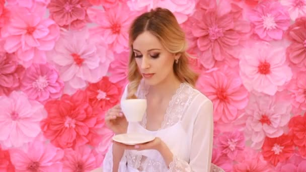 Young beautiful bride drinking from white cup on pink flowers background
