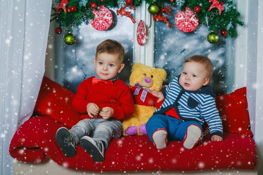 Two brothers sitting on new year decorated window