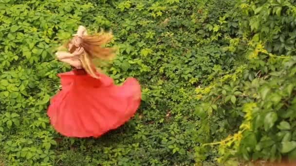 Gyönyörű fiatal nő, divat, piros ruhában pózol a zöld szőlő