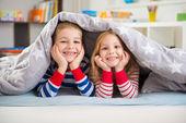 Dvě šťastné děti ležící pod dekou