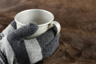 Hands in knitted gloves keep mug
