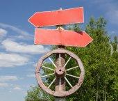 Fotografie Old waymark with cart-wheel