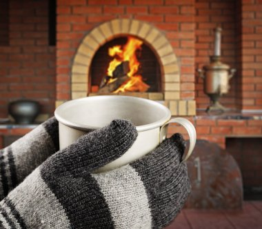 Hands in knitted gloves with mug