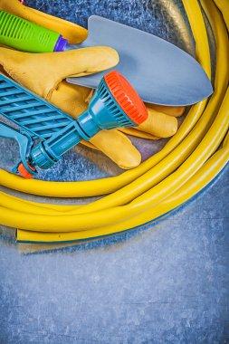 Garden hose, safety gloves and spade